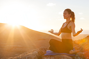 Girl doing yoga lotus position on the top of a volcano at sunset in Fuerteventura, Canary Islands