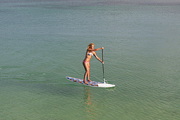 View of a pretty blonde girl in bikini paddling on a stand up paddle board