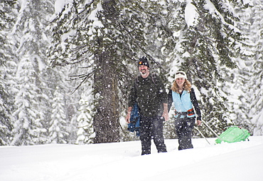 Smiling man and woman snowshoeing in snow storm, Sierra Nevada