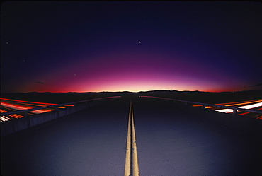A highway converging at a silhouette of some mountains, California, USA, United States