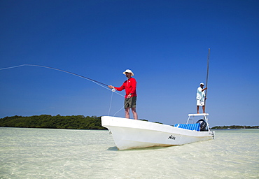 A man fly fishes in the clear waters off the coast of Belize, Belize