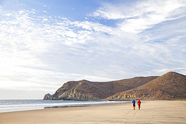 Two people walk down an empty beach under a blue sky, Mexico