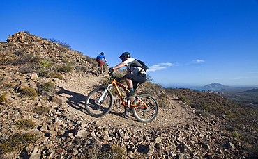 A mountain biker on a dirt trail surrounded by mountains and the occasional view of the ocean in the distance, Mexico