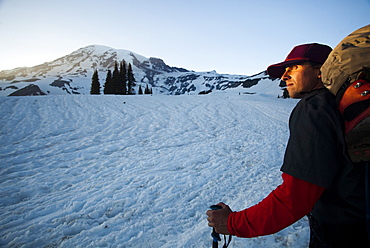A young skier skins up a snowy slope on Mount Rainier at sunset, United States of America