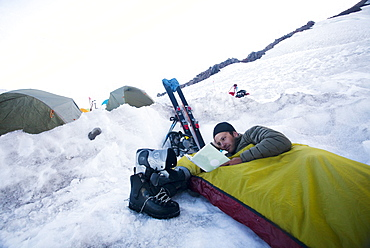 A young climber lies in his bivy sack and reads a book while the sun sets at base camp on Mount Rainier, United States of America
