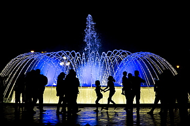 Visitors are silhouetted by a lit-up fountain at Reserva Park in Lima, Peru.