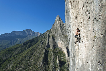 A man climbs up a limestone wall, with one of Potrero Chico's spires on the background.