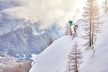 A man jumps down from a rock in the wood, during a cloudy ski morning in San Martino di Castrozza in the Dolomites