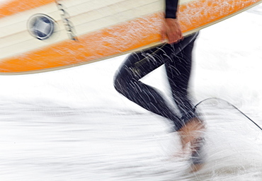 Close up of a Surfer carrying colourful surf board from the beach,Cornwall,UK