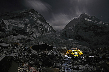 Night scene of a dining tent at the Everest Base Camp. The summit of Everest is blocked by part of the ridge that extends out on the left, while Nupste can be seen on the right of the picture. The infamous Khumbu ice fall can be seen as the rubble that pours out in the middle of the picture, Nepal