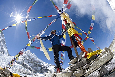 A Sherpa adding the finishing touches of a Puja, a traditional ceremony to appease the mountain gods for a safe passage for climbers attempting to scale Mount Everest, Nepal