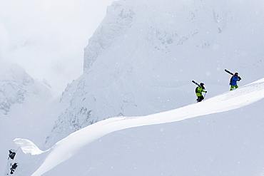 Ian McIntosh and Sage Cattabriga-Alosa hiking with skis on their backs in Haines, Alaska. April 2008, United States of America
