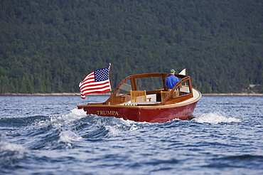 Senior man drives a power yacht in Somes Sound, Maine, United States of America