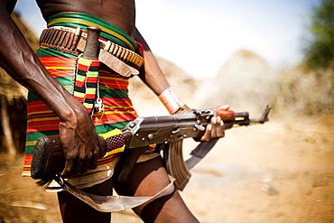 HAMER VILLAGE, OMO VALLEY, ETHIOPIA. An Ethiopian man holds a kalashnikov rifle at his waist, Ethiopia