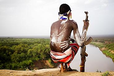 KARO VILLAGE, OMO VALLEY, ETHIOPIA. A young man holds his kalashnikov rifle while overlooking the Omo river in the remote Omo Valley of Ethiopia. (released: MHP_095_MR_RedKere), Ethiopia