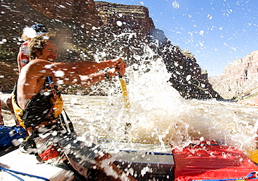 Raft guide, Marcus Cline gets splashed as he guieds his raft through the rapids of Cataract Canyon in Canyonlands National Park, Utah, United States of America