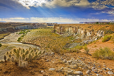 Crumbling cliffs line a canyon above Lake Powell in Big Water, Utah, just north of the Arizona boarder. Rain is clearly visible in the distance, United States of America