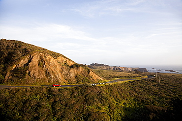 MENDOCINO, CALIFORNIA, USA. A red Prius, a hybrid vehicle, drives on a winding road along the shore of the California coast, United States of America