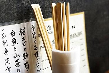 Restaurant menu, chopsticks in glass with napkins against wall, Tokyo, Japan, Japan