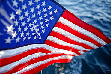 """American flag """"Stars and Stripes"""" floating onboard the Hydroptere, Long Beach, Los Angeles, United States of America."""