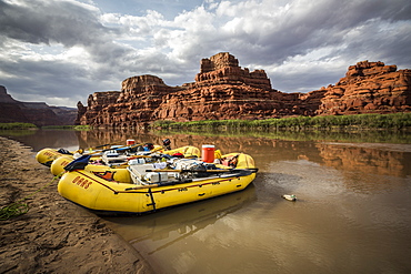 Rafts parked on the shore of a river in a desert landscape.