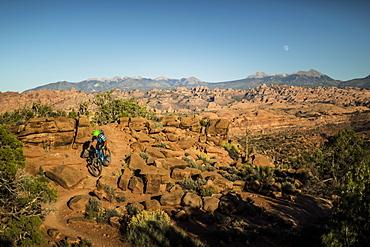 Man mountain biking on a trail in a desert environment.