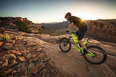Man mountain biking on a trail in a desert environment at sunset.