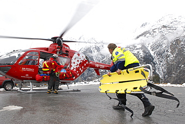 An ambulance paramedic is walking to a rescue helicopter to help an injured mountaineer that was flown down from a mountain after an accident.