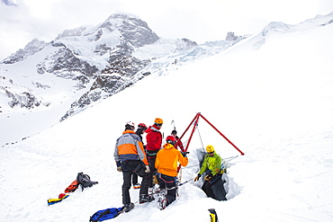 A mountain rescue technician is descending into a crevasse. When a skier breaks through the snow and tumbles down, the only way out is being winched out by the rescuers of Air Zermatt. In the background is the Breithorn mountain.