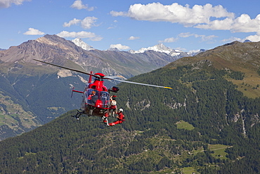 A mountain rescue emergency physician is hanging below a helicopter high above the ground. A injured hiker is being winched up. The Swiss Alps in the background.