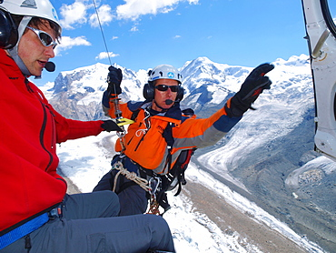 A mountain rescue technician is exiting a helicopter high above the ground. A winchman is ready to lower him down to the glacier where a climber is injured in a fall.