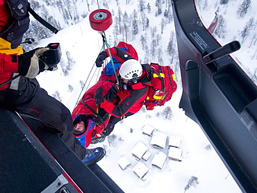 An emergency doctor and patient are being hoisted up to the rescue helicopter after a mountain accident.