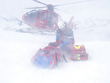 Rescue Personnel is helping an injured skier in the ski area of Zermatt in the Swiss Alps. The emergency doctor protects himself and the patient against the downwash of the landing helicopter.