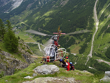 Mountain Rescue Personnel is carefully loading into a hovering helicopter.