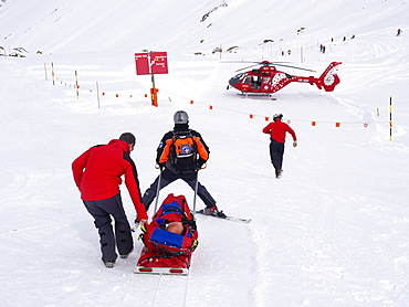 Rescue Personnel is helping an injured skier in the ski area of Zermatt in the Swiss Alps.