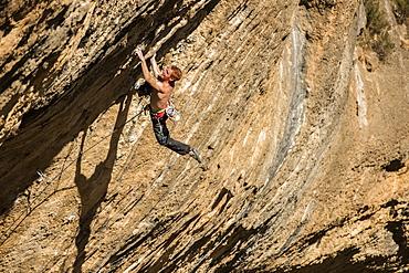 Professional italian climber Gabriele Moroni climbing an 8c route in Margalef, Spain.