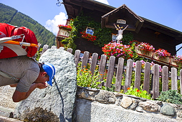A male hiker drinks water from a source in a village during the Glocknerrunde, a 7 stage trekking from Kaprun to Kals around the Grossglockner, the highest mountain of Austria.