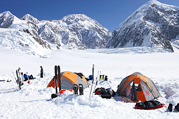 A team of mountaineers is resting in their camp with tents on the lower Kahiltna glacier on their way to Mount McKinley in Alaska.