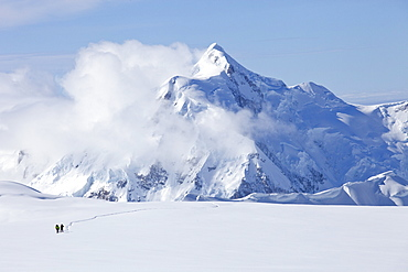 Two mountaineers are crossing a glacier on Mt. McKinley, Alaska. Mount Hunter is in the background.