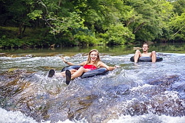 A young couple tubes down a river.
