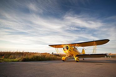 Old yellow bi-plane on the runway