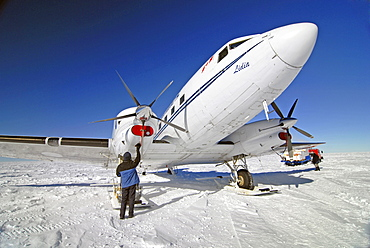 A ski equipped aircraft is being prepared for takeoff near the South Pole.