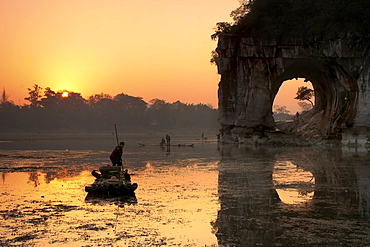 Chinese fisherman on a bamboo raft in Li Jang River, Yangshuo, Guilin, Guangxi region, China.