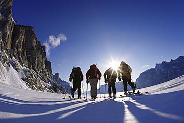 four skiers traversing across frozen fjord near Baffin Island, Canada