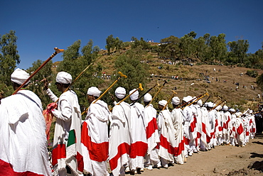 Group of priests dressed in ceremonial clothes chanting and dancing in procession during Timkat festival in Lalibela, Ethiopia
