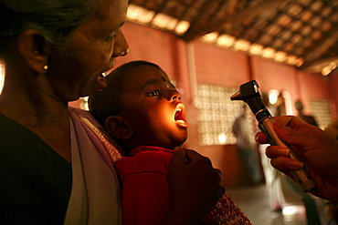 A young Sri Lankan boy 'opens wide' as a doctor peers into his mouth, Kalmunai, Sri Lanka.