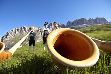 Alphorn players in traditional outfits on the side of the road at Passo Pordoi (2239 m), the second pass of the Maratona dles Do