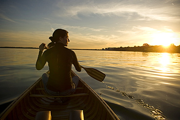 Maure Woman Sits In Front of Wood Canvas Canoe On Lake Looking Off Into The Sunset Holding Paddle