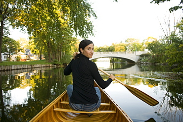 Mature Woman Sitting In a Wood Canvas Canoe in a City Environment Looking Over Shoulder In Between Paddle Strokes