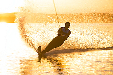 A woman water skis on Whitefish Lake at sunset in Whitefish, Montana.